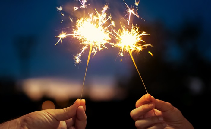 two hands hold sparklers