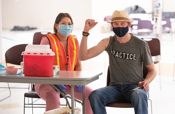 A health care worker sits next to someone they just vaccinated.