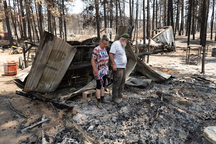 Two people stand in a pile of burned scraps, looking down.