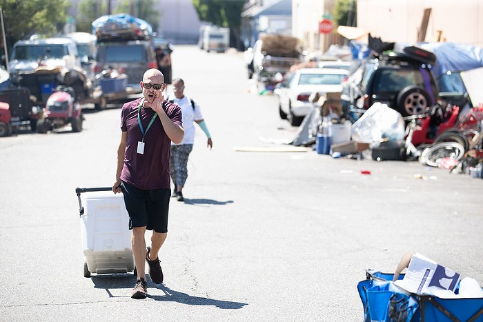 A man walking down a street lines with tents, rolling a cooler behind him. He has his hand cupped around his mouth and is talking loudly about having water and cooling supplies,
