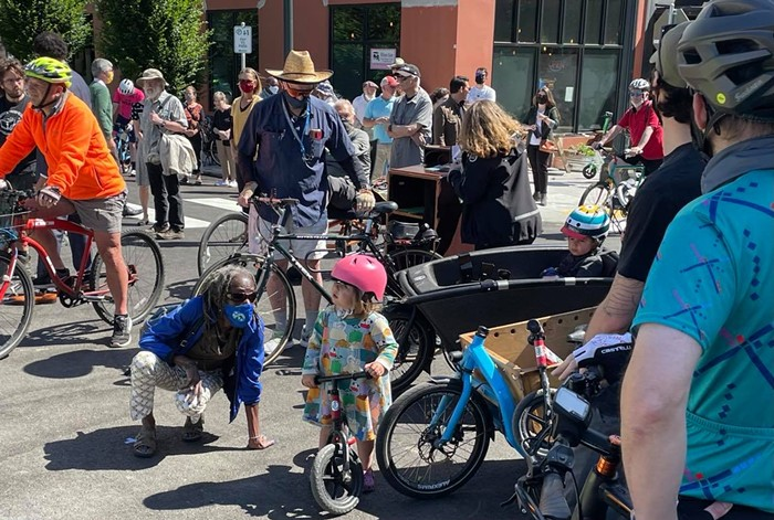 Hardesty crouches down to talk to a child. The stand in front of a large group of bicyclists preparing to ride across the new bridge.
