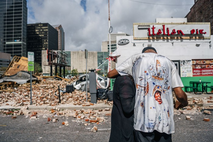A couple hugs each other in front of a demolished storm. There are bricks scattered around and the building is leveled from the hurricane.