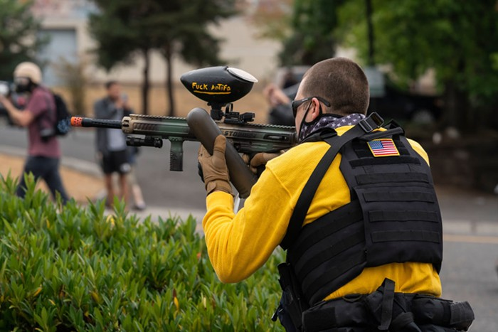 A member of the far-right group Proud Boys fires a paintball gun on August 22.