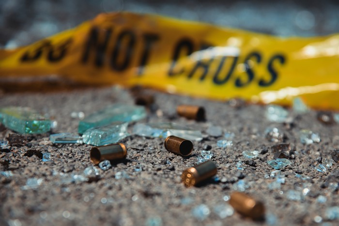Gun casings scattered on the street at a crime scene.