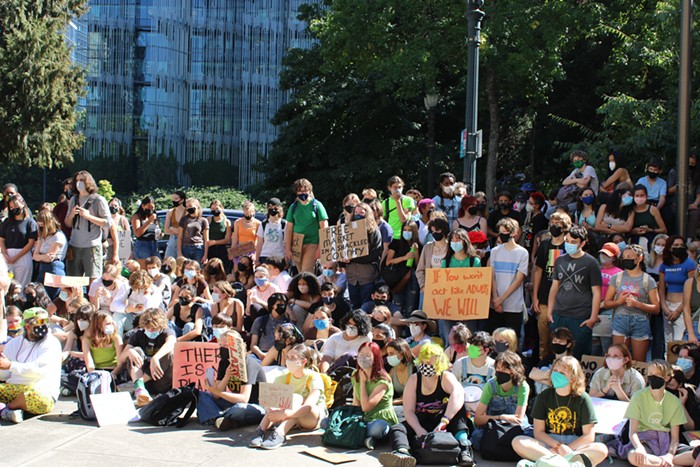 a large group of youth holding signs for climate justice