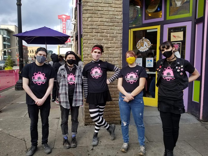 Five Voodoo Doughnut employees stand in front of the store.