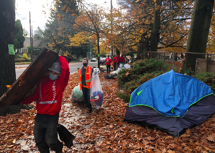 A city crew removing items from a homeless encampment from a public sidewalk in November 2020.