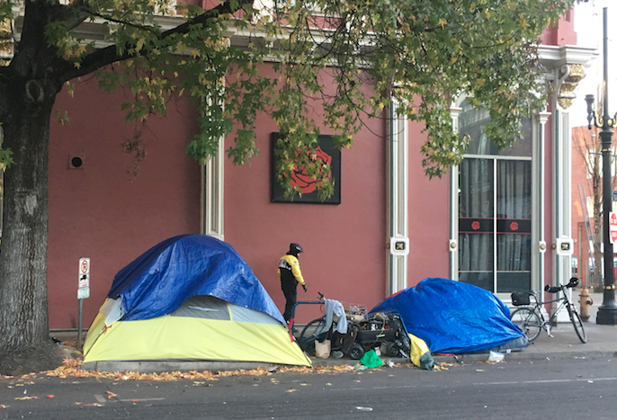 A couple tents covered in blue tarps on the sidewalk. A police bike officer walks by.