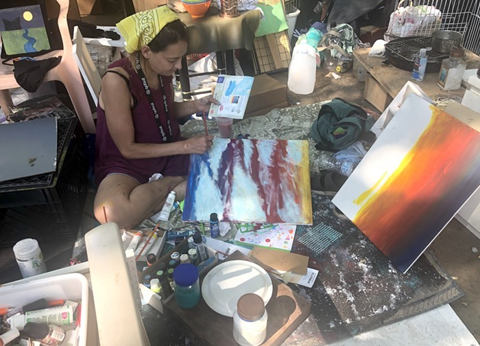 A woman sits on the ground, painting. She is a resident at the Laurelhurst camp.