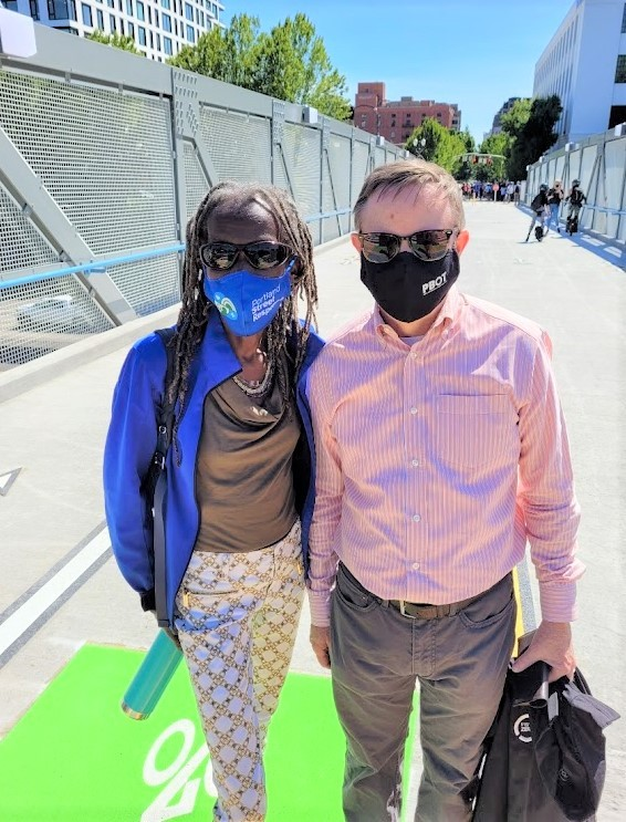 Hardest stands next to a man. They are both wearing masks