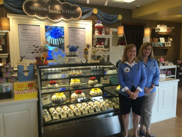 Twin sisters Jannette Neely (right) and Penelope Ritchie (left) stand in front of the bundt cake show case inside of their Nothing Bundt Cake franchise in Town and Country, Missouri. - EMILY MCCARTER