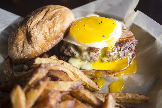 "The ""Wake and Bake"" burger tops an eight-ounce patty with pork belly confit, hollandaise aioli and a sunny-side up egg. - PHOTO BY MABEL SUEN"