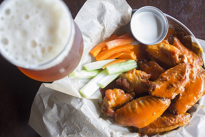 Beer-brined wings are fried, then topped with classic buffalo sauce. - PHOTO BY MABEL SUEN