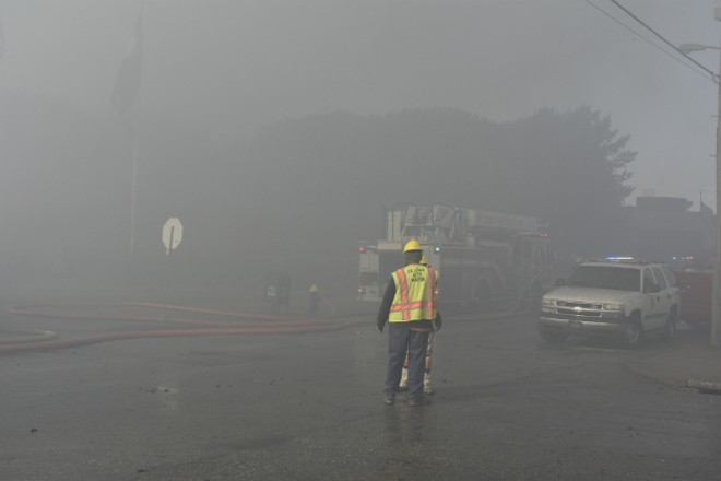 A city worker stands on Park Avenue during a major fire in a nearby warehouse. - PHOTO BY DOYLE MURPHY