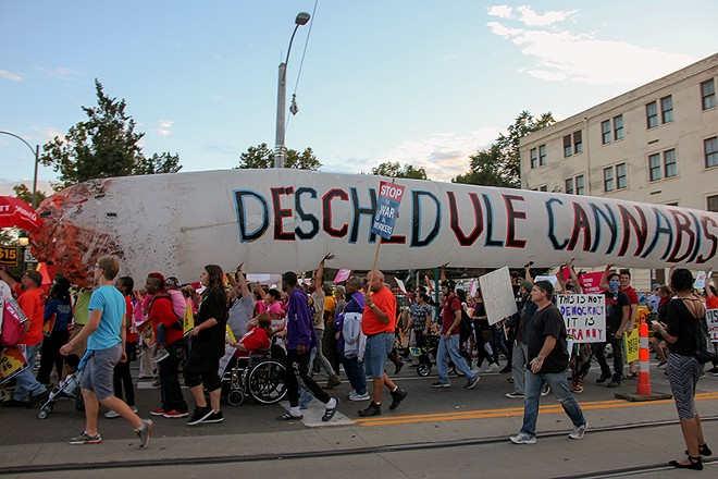 Legalization supporters carry a giant inflatable joint near the site of the 2016 presidential debate in St. Louis. - PHOTO BY DANNY WICENTOWSKI