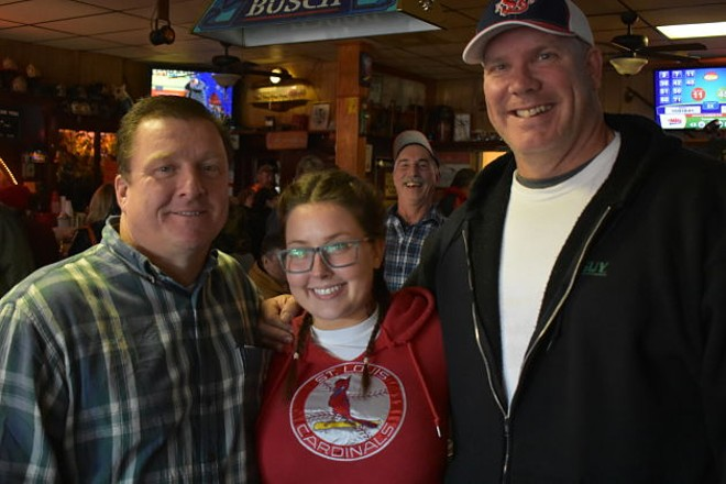 """Ken Mitchell, Sarah Stippec, a photo-bombing regular and Kent """"Biggin"""" Cox drinking at the bar on Wednesday. - PHOTO BY DANIEL HILL"""