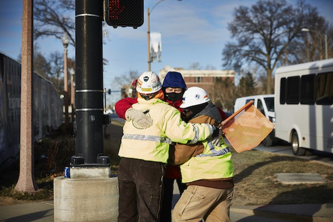 A passerby gives the ladies a hug on January 5, a day when temperatures were well below freezing. - THEO WELLING