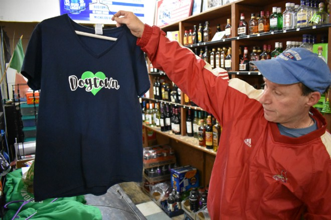 Patrick Wrzesinski, owner of Patrick's Dogtown Liquors, holds up a bullet-pierced T-shirt from a burglary. - PHOTO BY DOYLEMURPHY