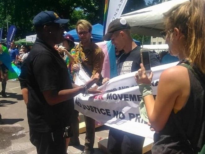 Justin Michalik, center right, holds a protest banner at the Monsanto booth shortly before his arrest on June 26. - PHOTO COURTESY OF JUSTIN MICHALIK
