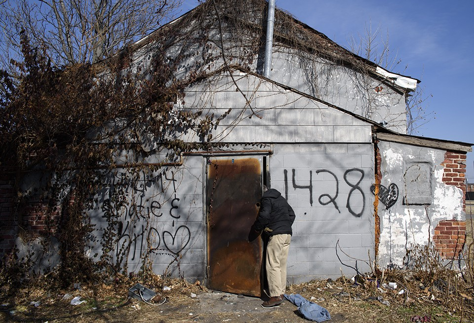 Chris Ohnimus checks for anyone inside an abandoned building near the vacant Carr School building during a winter patrol outreach on February 8. - NICK SCHNELLE