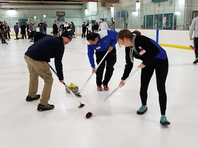 Curling novices sweep the ice in front of the granite stone during an instructional group session from the St. Louis Curling Club. - ALLISON BABKA