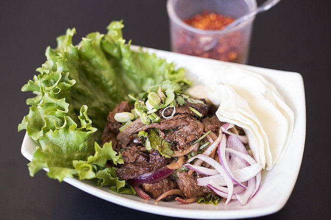 Nam tok beef offers grilled slices of steak, cilantro, red and green onion, in chile lime sauce. - MABEL SUEN