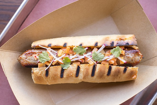 Rabbit sausage is topped with pickled carrot, local radish and cilantro. - MABEL SUEN