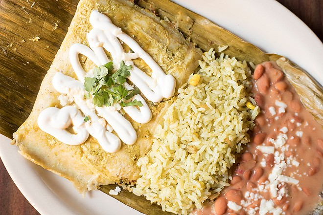 Chicken and salsa verde tamales are topped with sour cream and served with pinto beans and rice. - MABEL SUEN