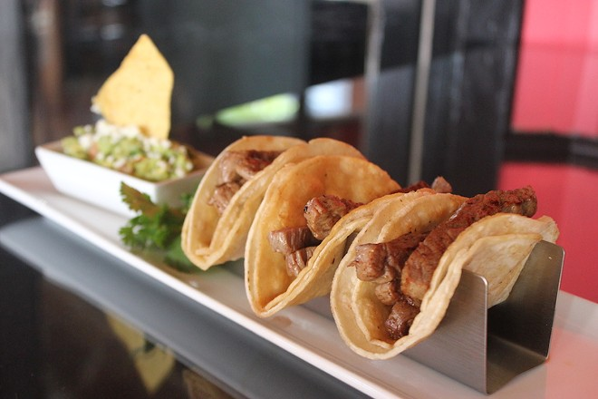 Street tacos are made with tender flank steak and served with cilantro, lime and a side of guacamole. - SARAH FENSKE
