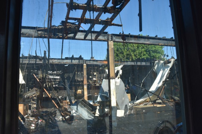 A view through the window of Macklind Avenue Deli shows the damage. - DOYLE MURPHY