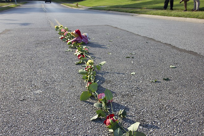 A line of roses arranged on portion of street where Brown was killed. - DANNY WICENTOWSKI