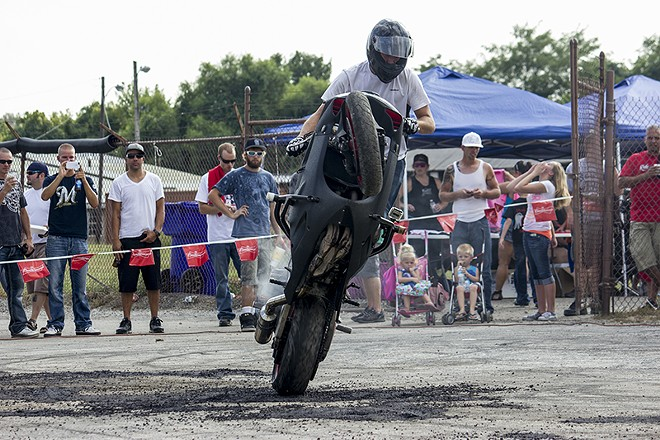 A rider pulls a wheelie during a 2013 Ride of the Century event in Columbia, Illinois. - DANNY WICENTOWSKI