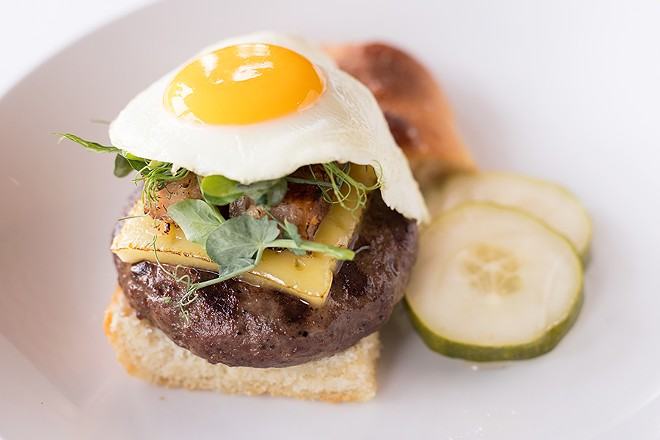 The burger is topped with a fried chicken egg and served on sea-salt foccacia with house pickles. - MABEL SUEN