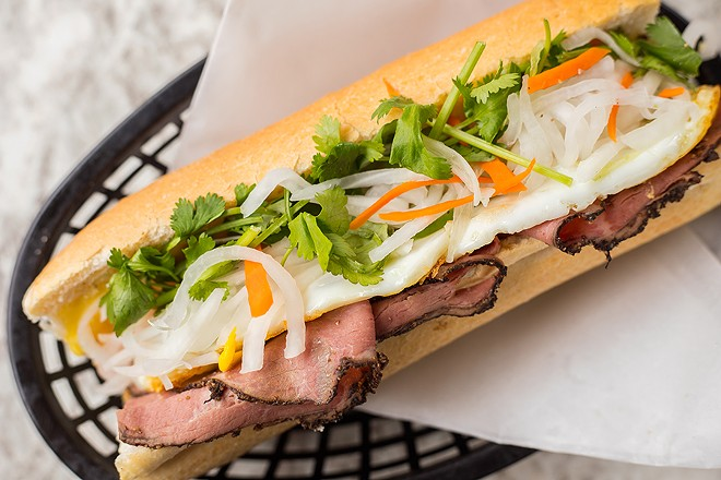 The beef pastrami bánh mì is topped with a sunny-side-up egg, pork pâté, pickled radish and carrots, jalapeño, cucumber and cilantro. - MABEL SUEN