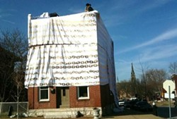 Update: See photos of the final installation here. Spandex patterned in gold chains covers the home at the corner of Iowa and Arsenal streets. - PHOTOS: CHAD GARRISON