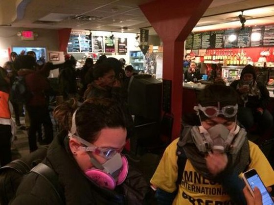 Occupants of MoKaBe's strapped on gas masks after tear gas seeped into the coffeehouse on November 25. - TWITTER