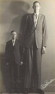 Wadlow standing next to his father.