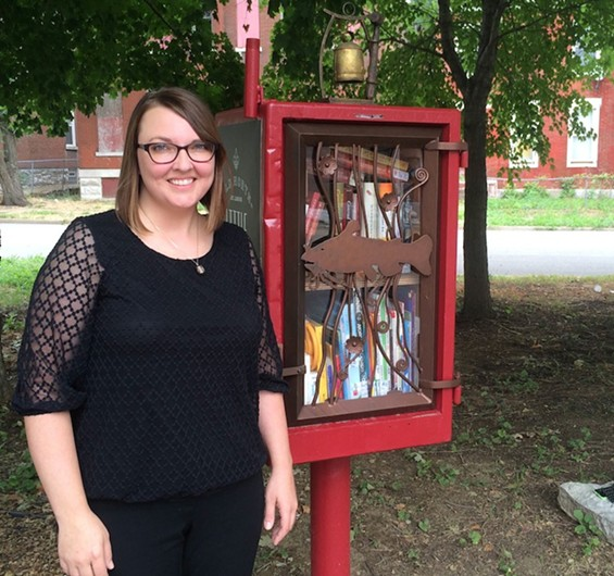 Gina Sheridan stands next to the free library she helped established in an Old North St. Louis park.