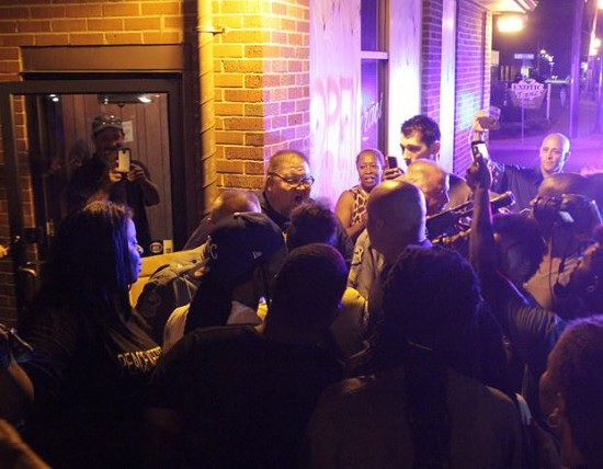 Cops put themselves between a Darren Wilson supporter and Michael Brown protesters. - DANNY WICENTOWSKI