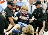 Cindy Sheehan is carried away from her protest position.