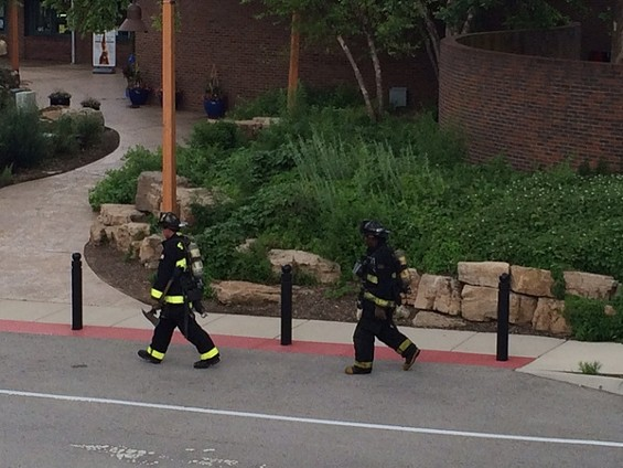 Firefighters with gear and oxygen tanks walk back to the firetruck once the blaze is put out.
