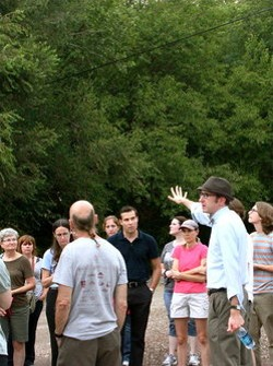 Michael Allen, in hat and bow tie, leads tours into the Pruitt-Igoe site.  - LEAH GREENBAUM