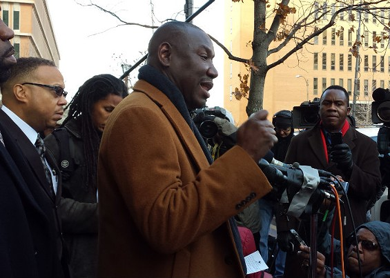 Brown family attorney Benjamin Crump, center, and attorney Anthony Gray, left, address the media. - JESSICA LUSSENHOP