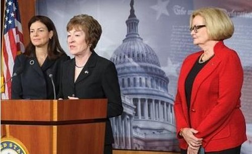 Senator Susan Collins, at the podium, stands with Senator Claire McCaskill, on the right.