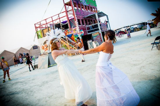 "Jessica Bergen and Noelle Foreman, of Washington, spin in circles before their individual weddings in front of their Burning Man camp ""Do-More-Now's Firehouse."" - SARAH CROSS"