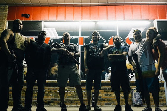 Mike Gutierrez (left) and Adam Weinstein (third from left) brought guns to guard their store during the riots in Ferguson last night. - BRYAN SUTTER