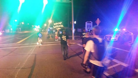 Demonstrators, closely followed by press, walk up and down W. Florissant Avenue. - DANNY WICENTOWSKI