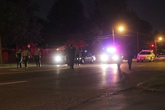 Police move south after clearing a stretch of West Florissant Avenue Monday night. - DANNY WICENTOWSKI