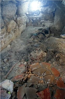 The tomb of K'abel, Supreme Warrior and Snake Lord. Her skull peeps up just above the plate fragments. - EL PERÚ-WAKA' ARCHAEOLOGICAL PROJECT