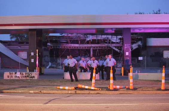 Police guard the burnt-out, graffitied QuikTrip in Ferguson. - DANNY WICENTOWSKI